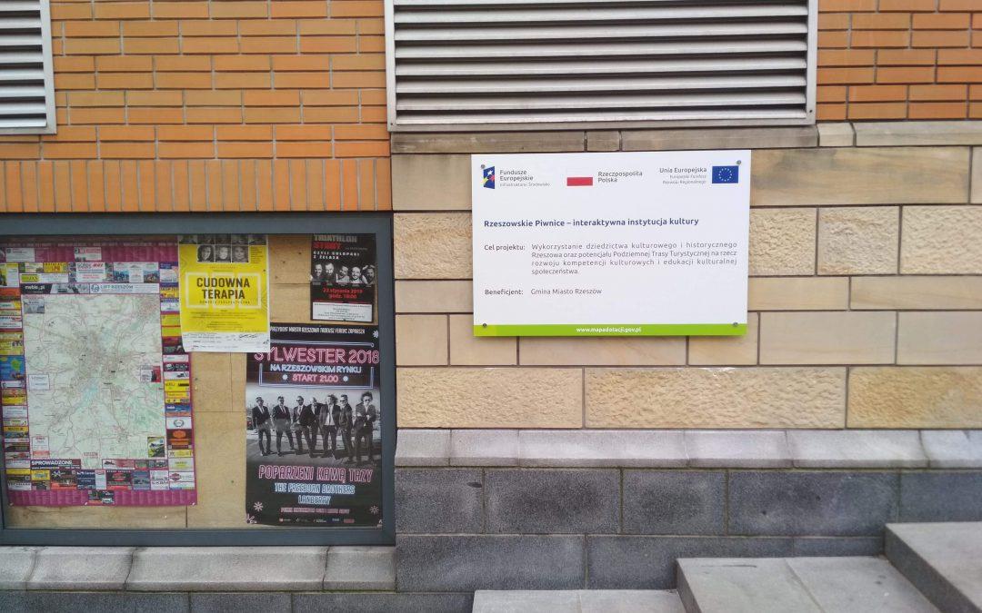 Wykonanie imontaż tablicy informacyjnej  przy wejściu dobudynku Podziemnej Trasy Turystycznej wRzeszowie